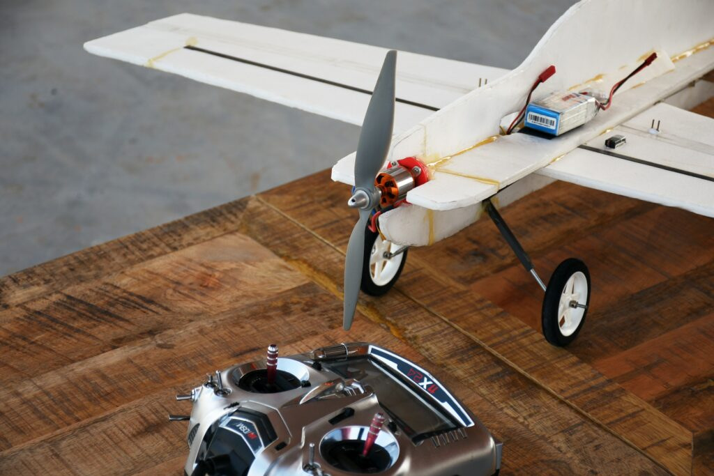 An R/C plane on a table with a radio control.